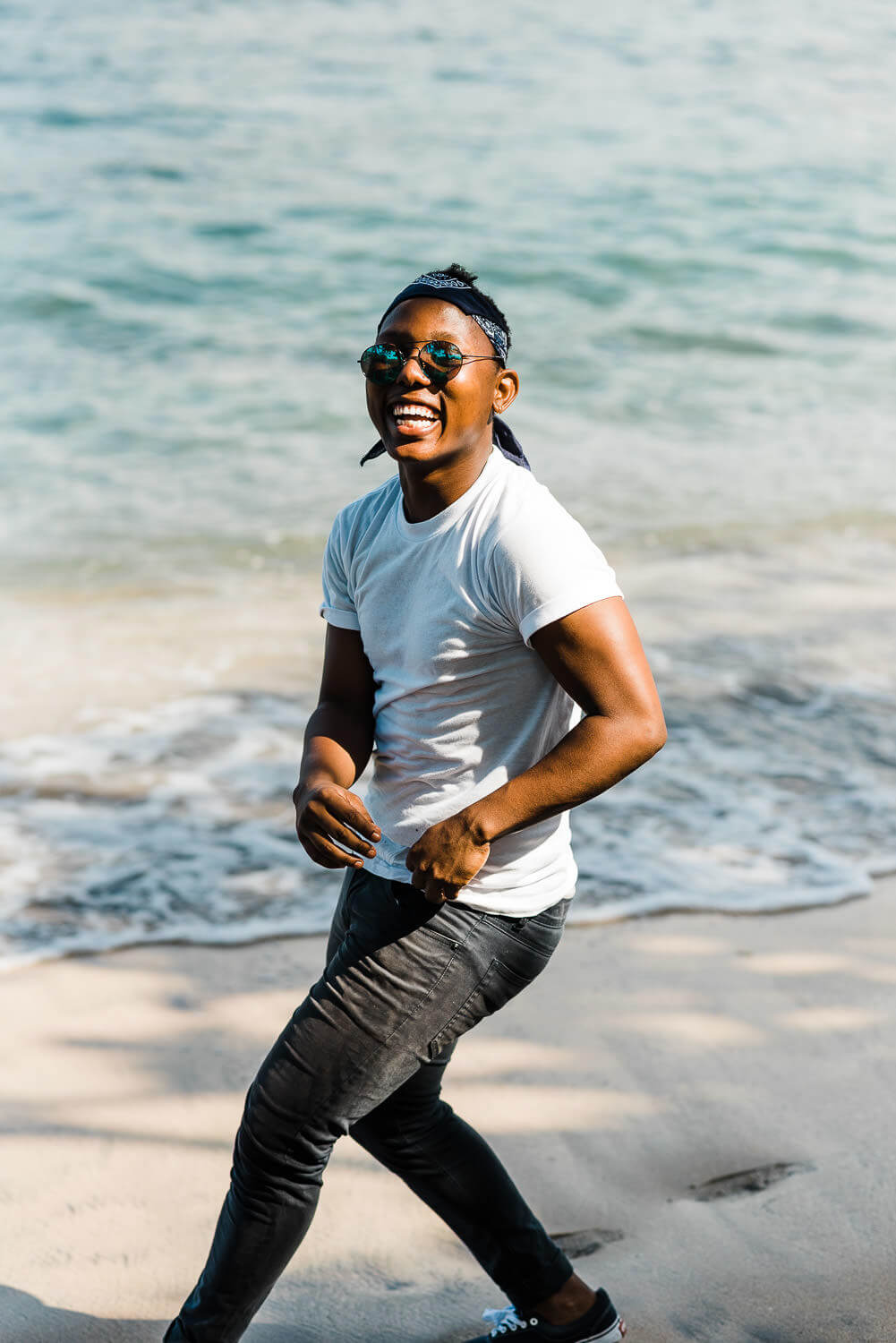 Young man laughs while running on the beach in the Caribbean