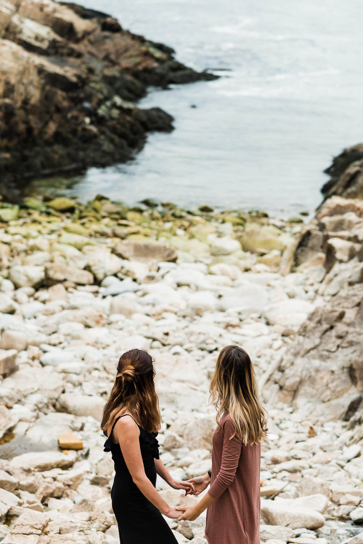 Two women holding hands near the ocean