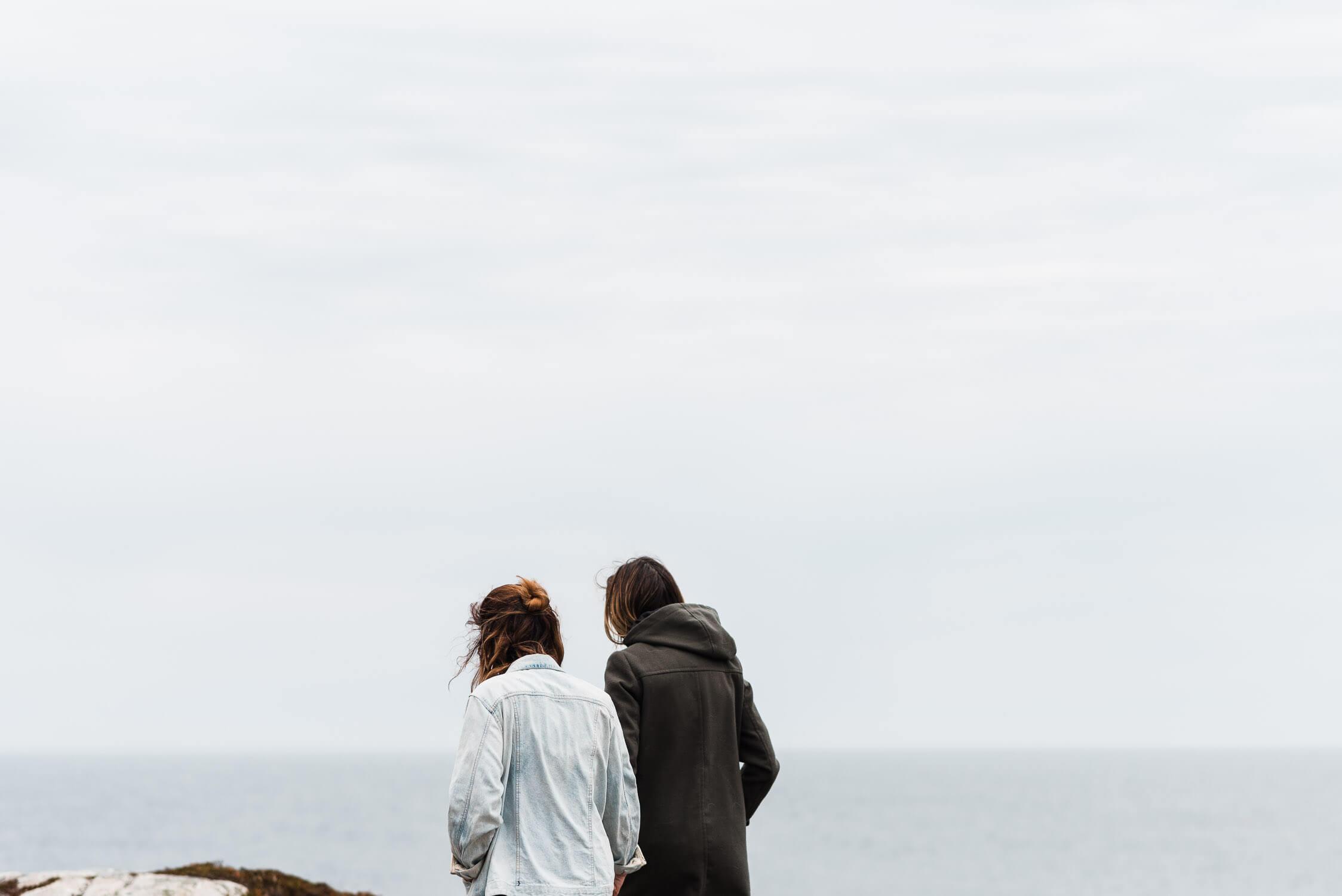 Two girls walking away towards the ocean