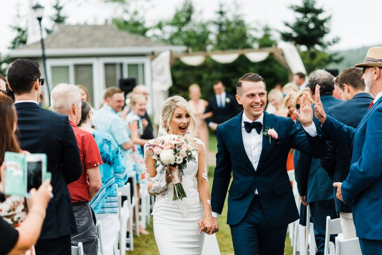 very excited bride and groom walking away from wedding ceremony