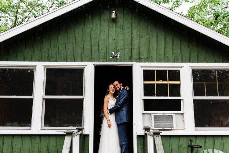 bride and groom standing in the doorway of green cabin