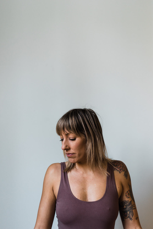Halifax yoga instructor wearing purple shirt leaning against light grey wall