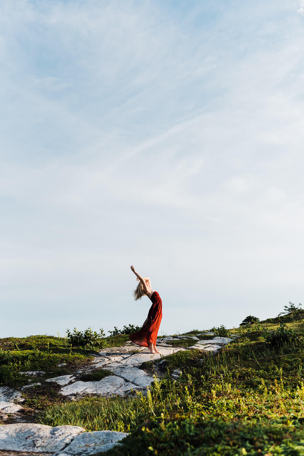 Blonde haired model wearing red dress posing on rugged landscape of Duncan's Cove near Halifax