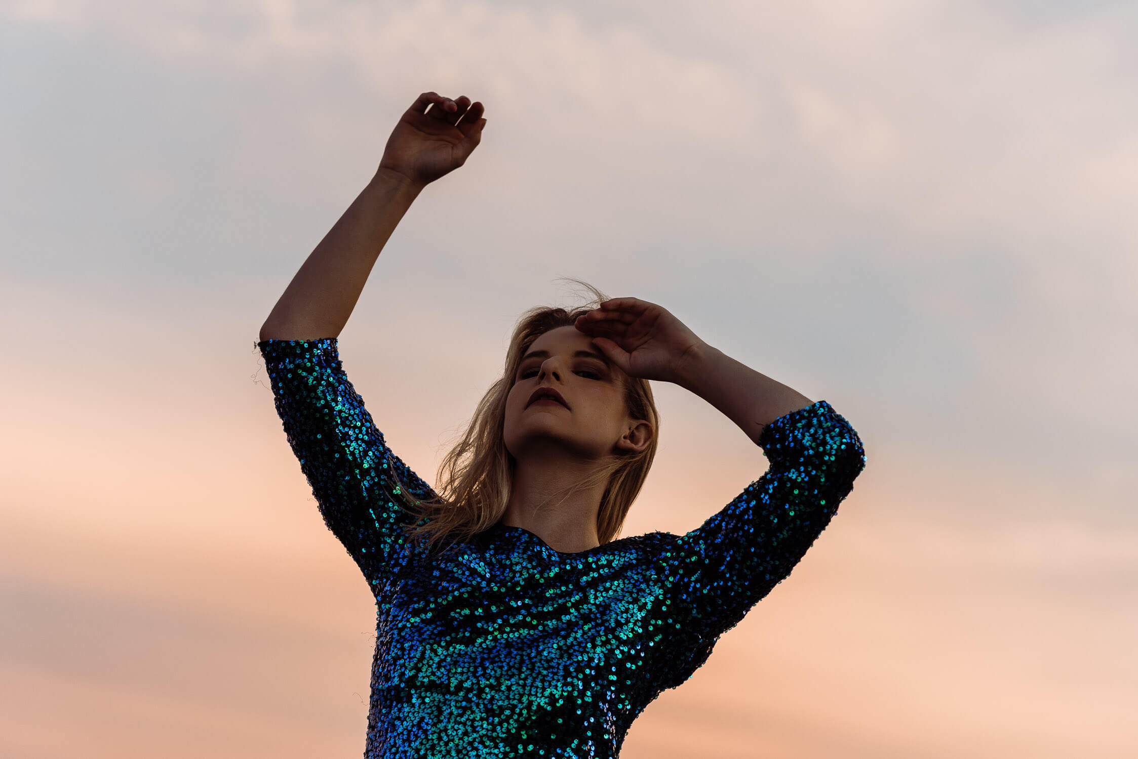 Female model wearing blue and green sequin dress at sunset