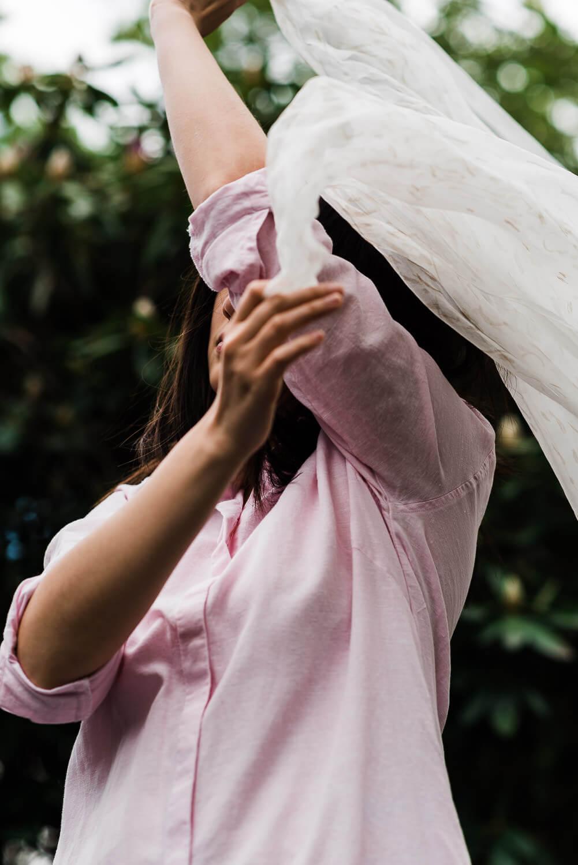 woman in pink dress swirling white sheer fabric around her