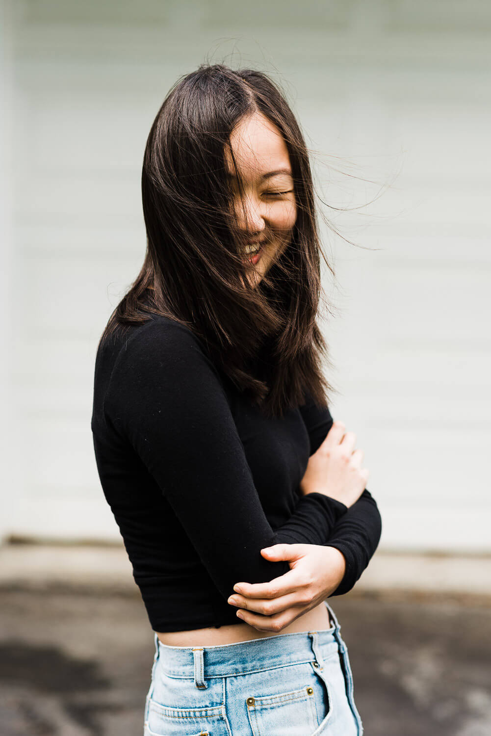 Young woman laughs as the wind blows her dark hair