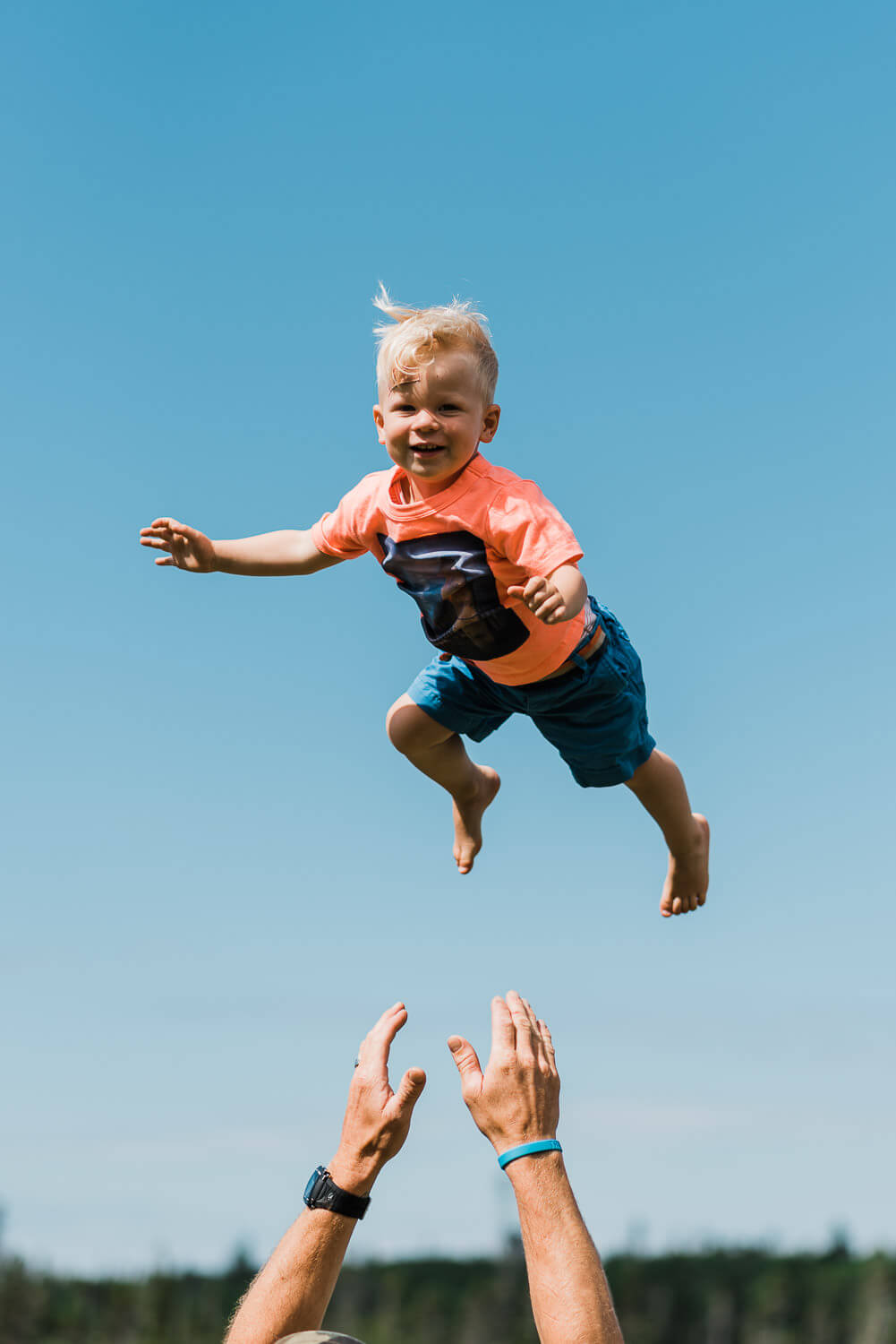 Boy laughing while his father throws him up in the air