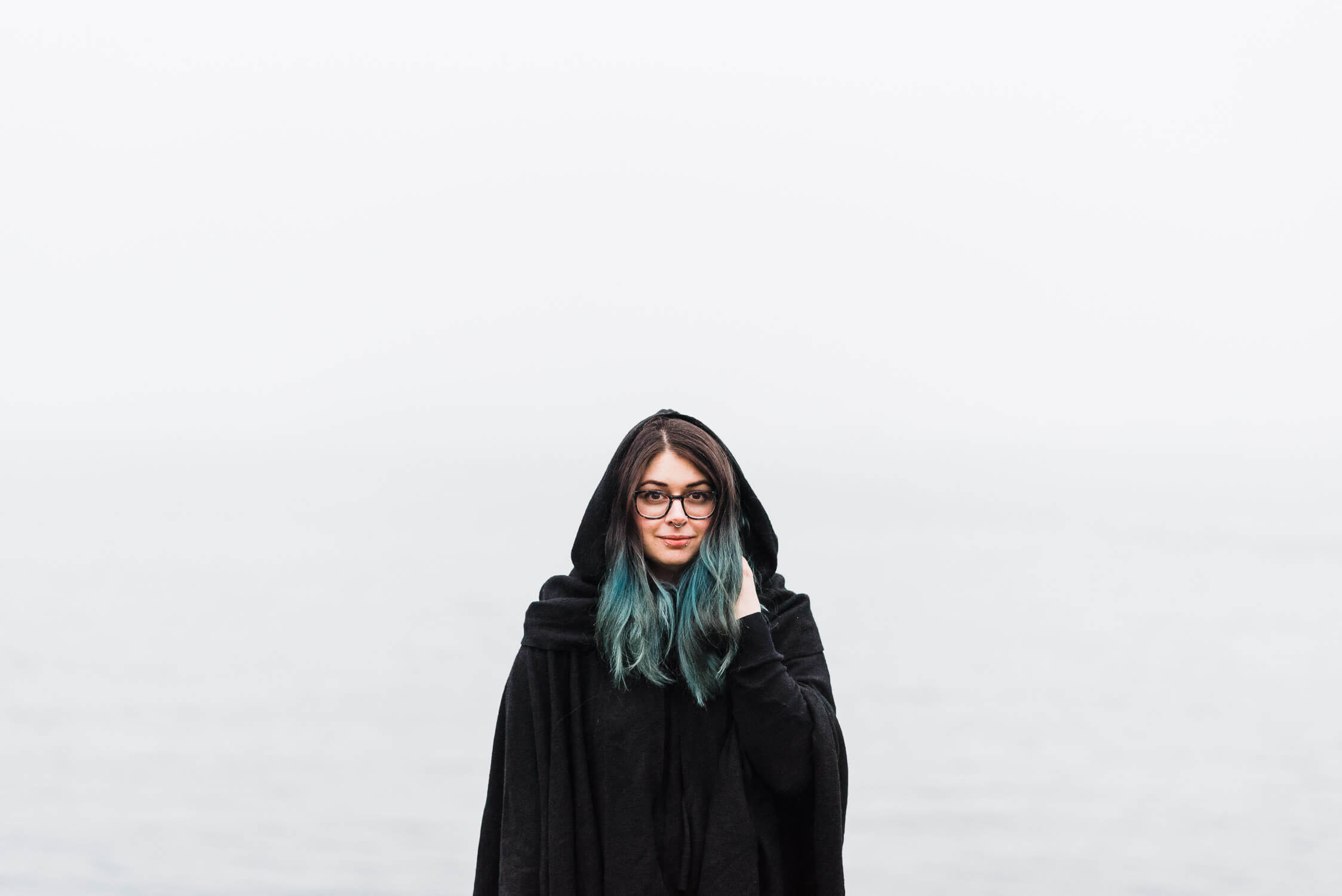 Blue haired woman wearing black cape standing on the foggy coastline of Dartmouth, Nova Scotia