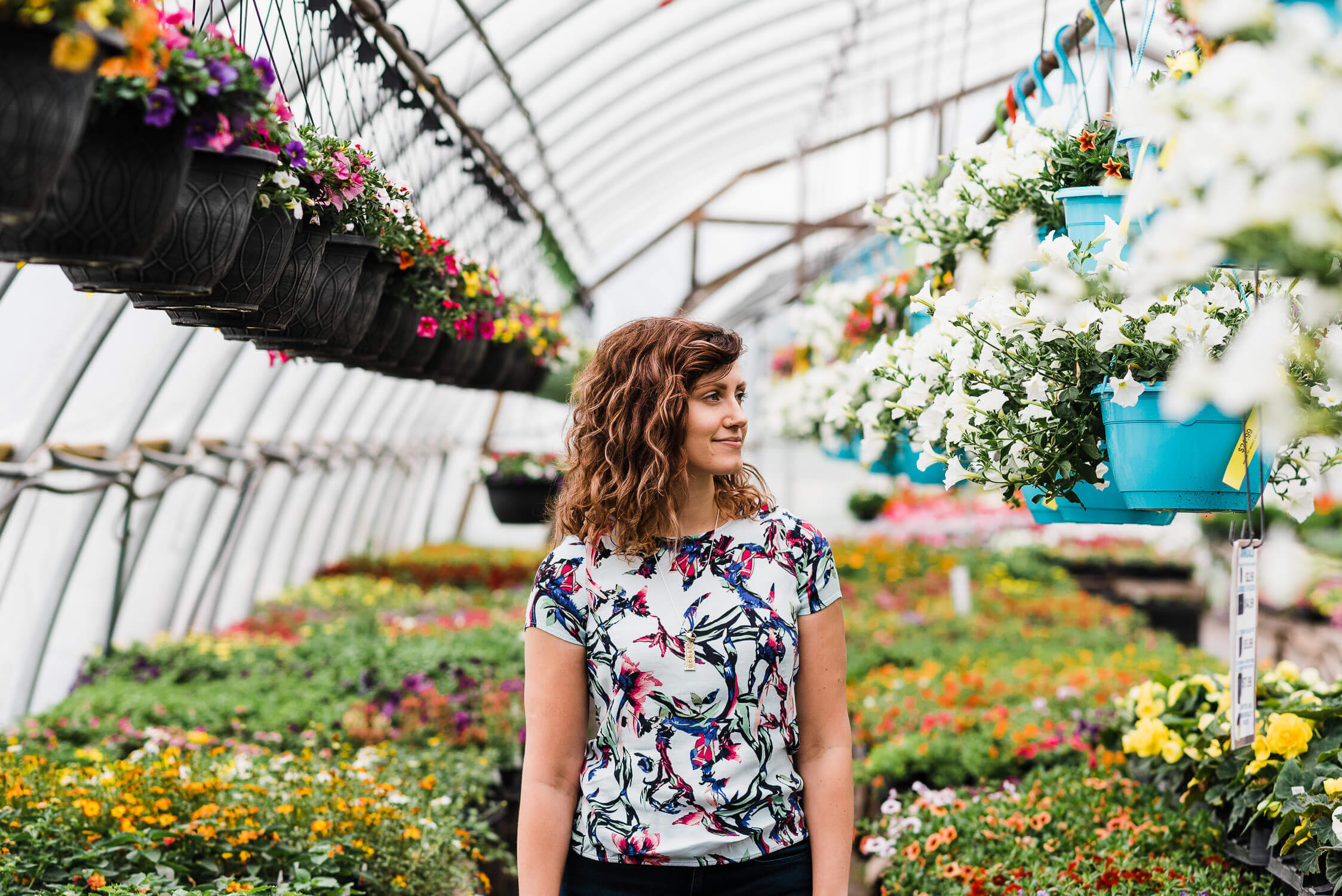 Young woman wearing colourful shirt stands in greenhouse full of colourful flowers