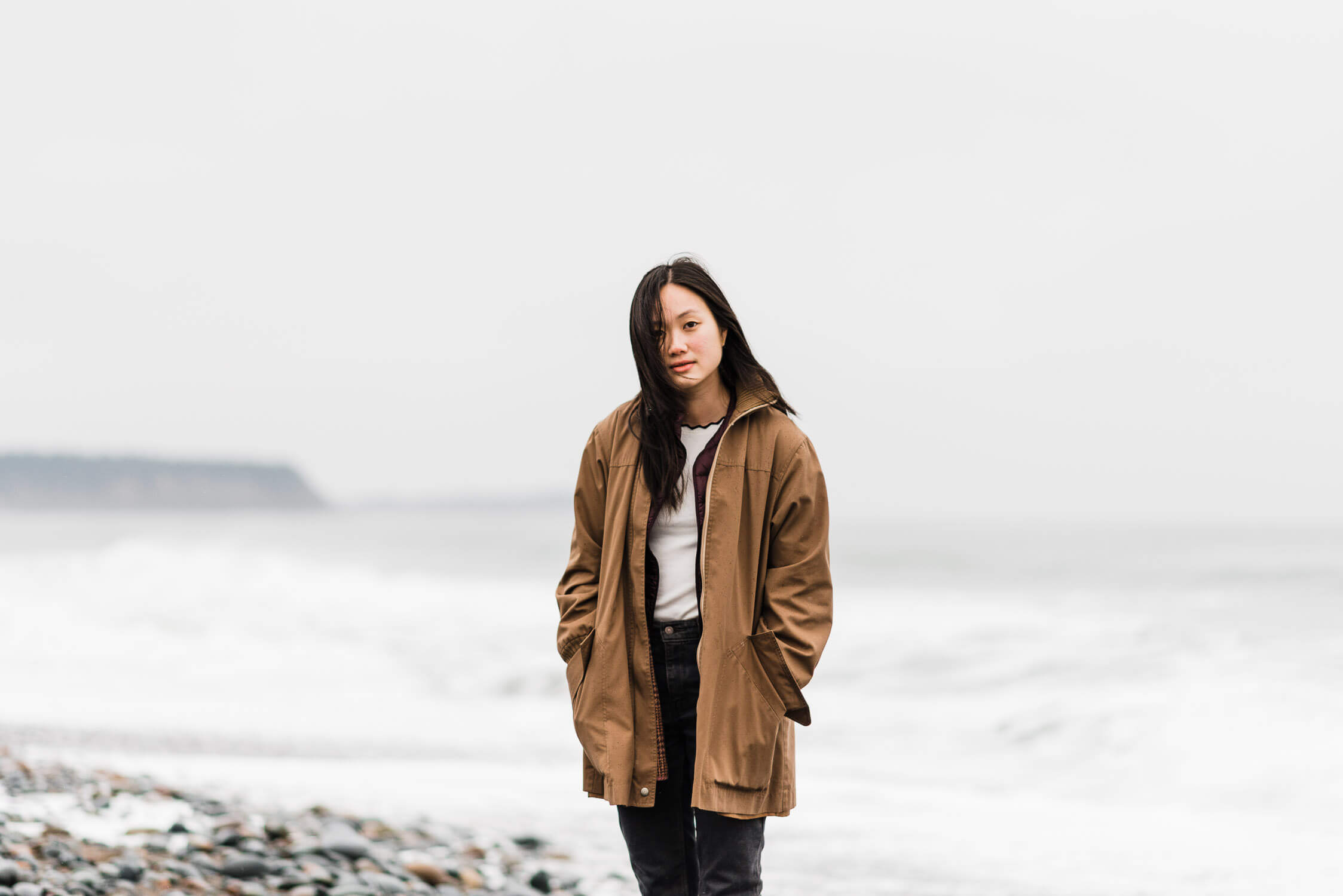 Woman in tan jacket stands on the foggy shore of Lawrencetown Beach