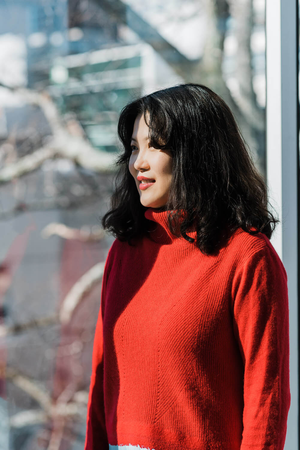 Woman in bright red sweater stands next to window while the sun shines on her face