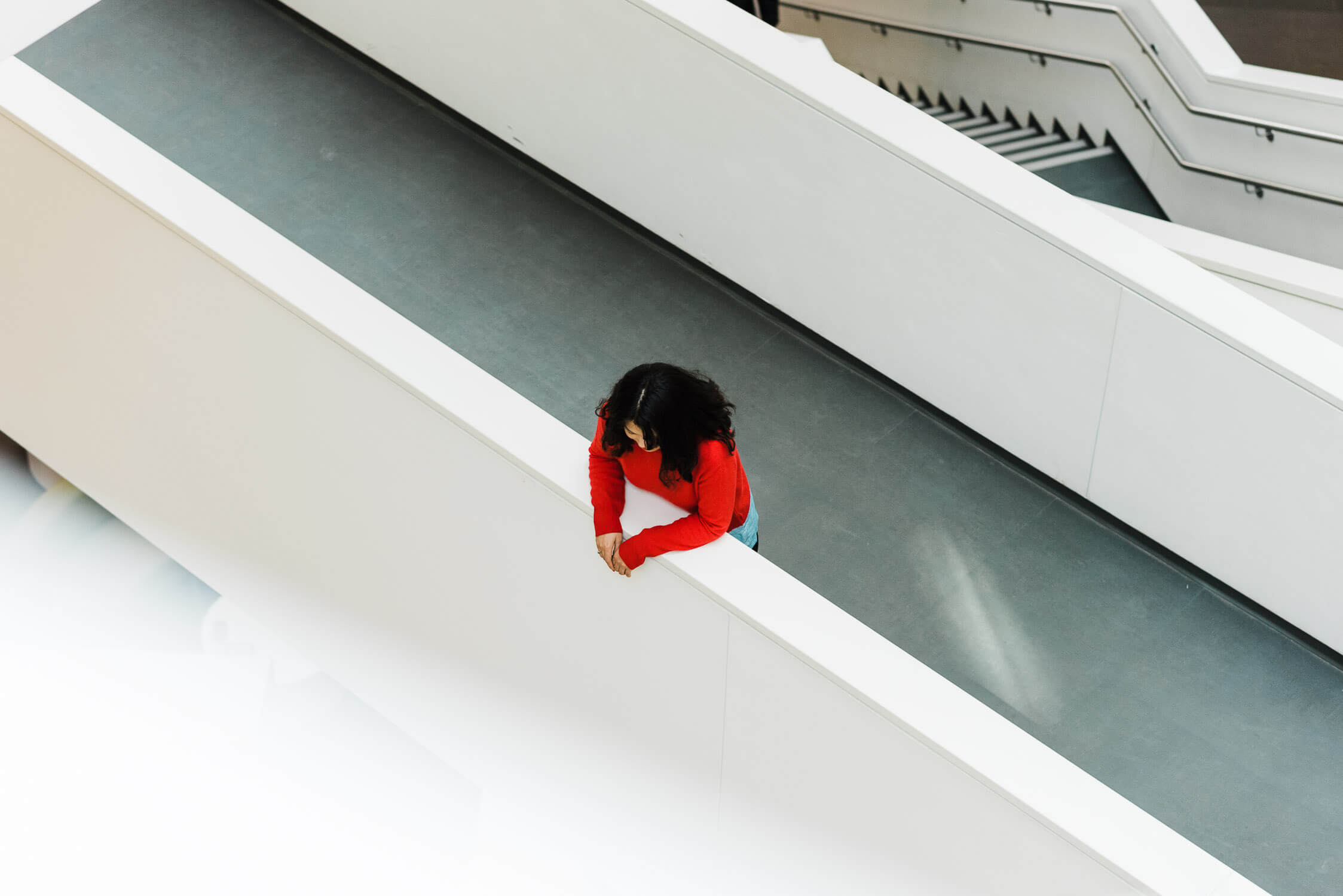 Woman in bright red sweater stands on the walkway at the library