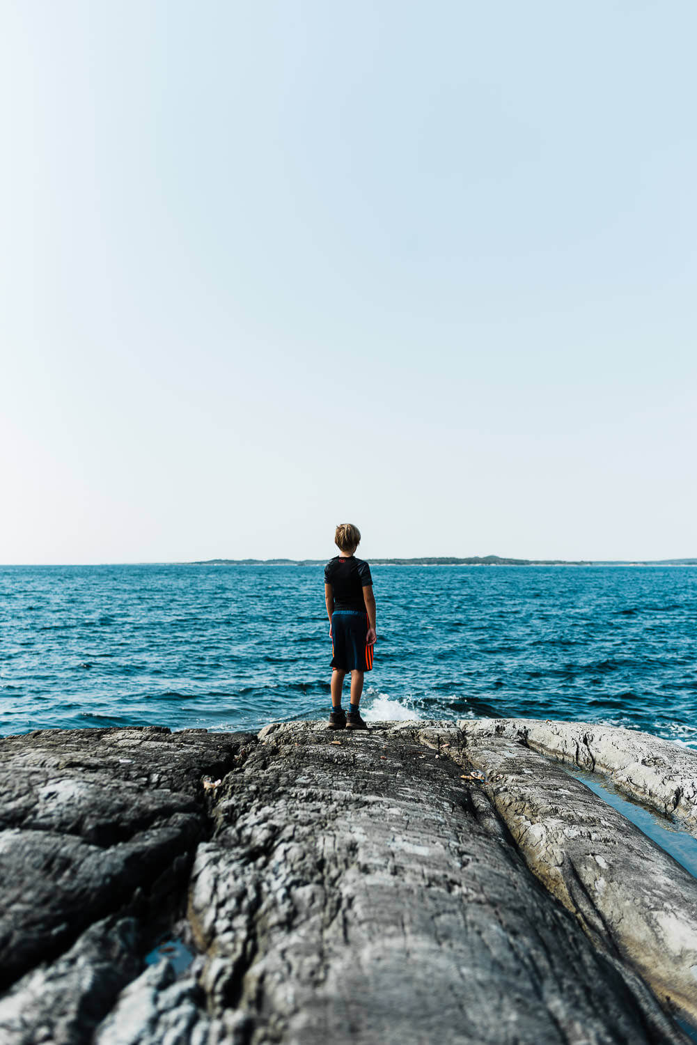 Boy stares out at the blue ocean on Taylor Head hiking trail