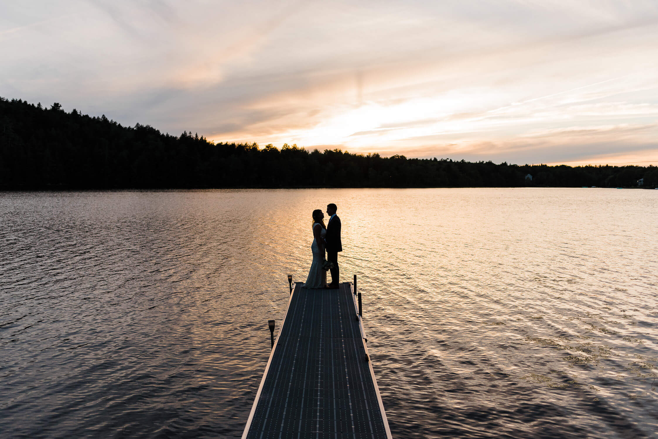 Bride and groom standing at the edge of dock at sunset