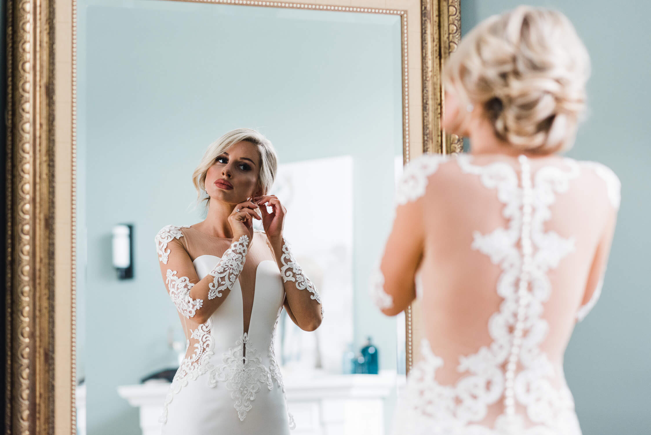 Bride gets ready for wedding by putting on earrings