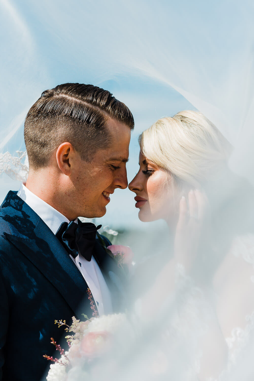 bride and groom standing close as veil blows in the wind