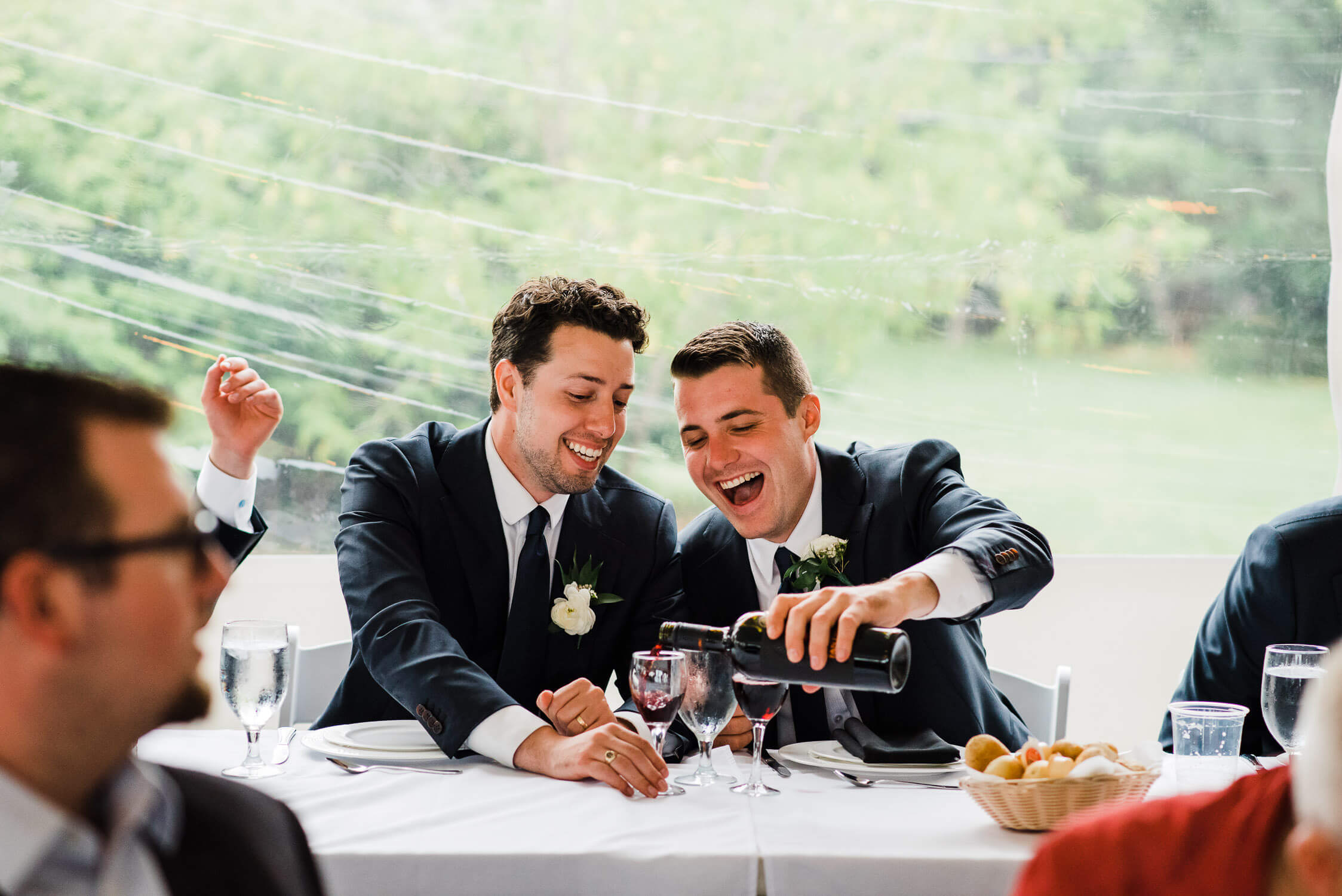 Groomsmen laughing as they help themselves to a drink at the reception