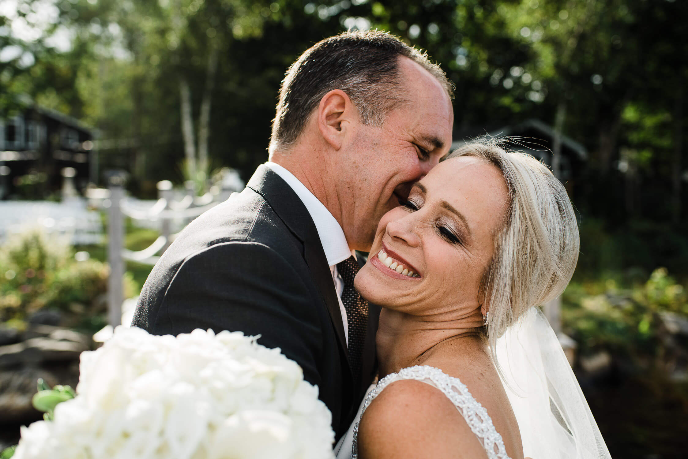 Newlyweds hugging and laughing on the dock of their lakefront home