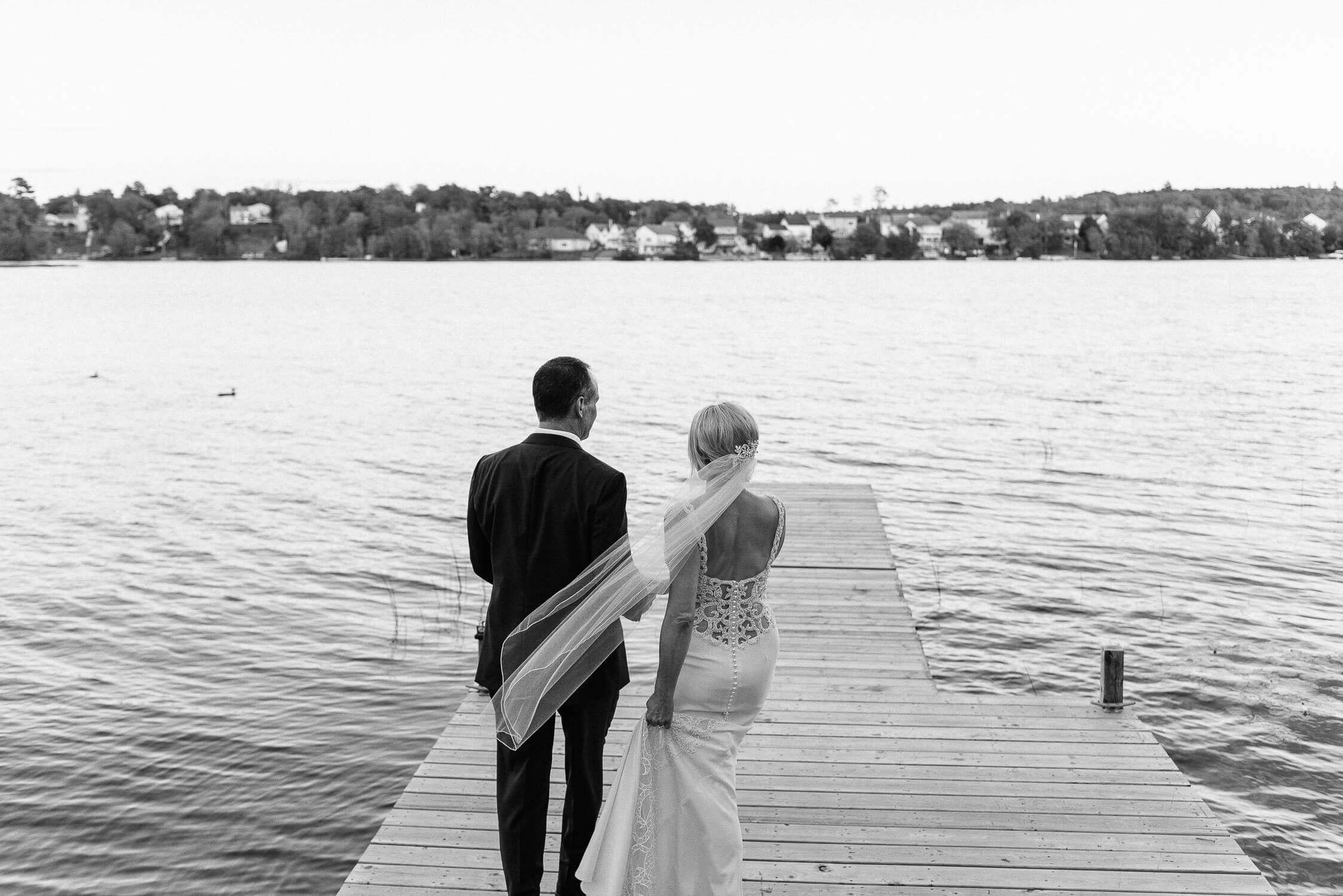 wedding couple standing on the dock of their lakeside home