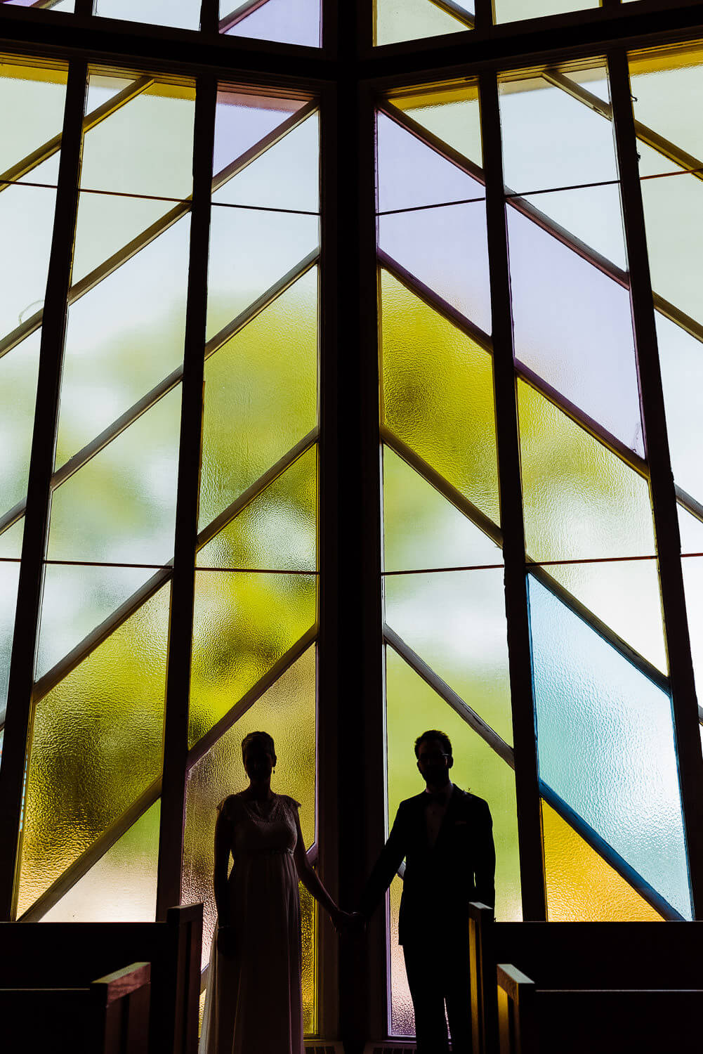 silhoutte of man and woman standing in front of stained glass window in church