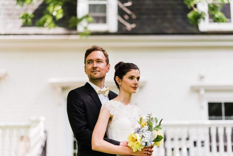 bride and groom stand in front of old country home in grand pre nova scotia