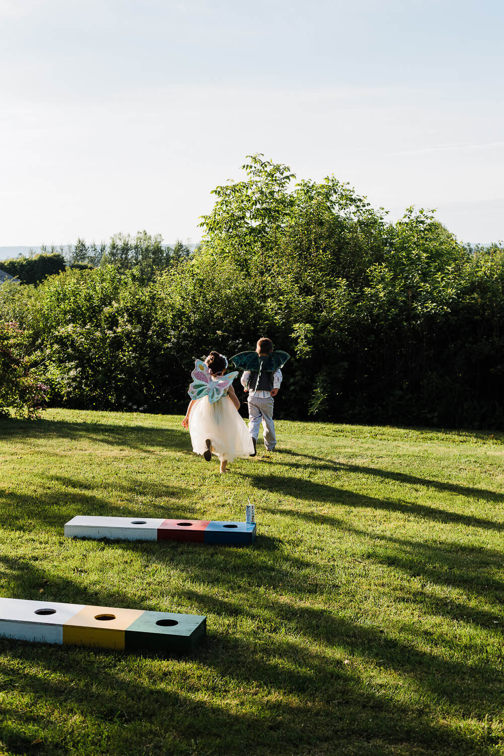 kids at summer wedding running on the lawn