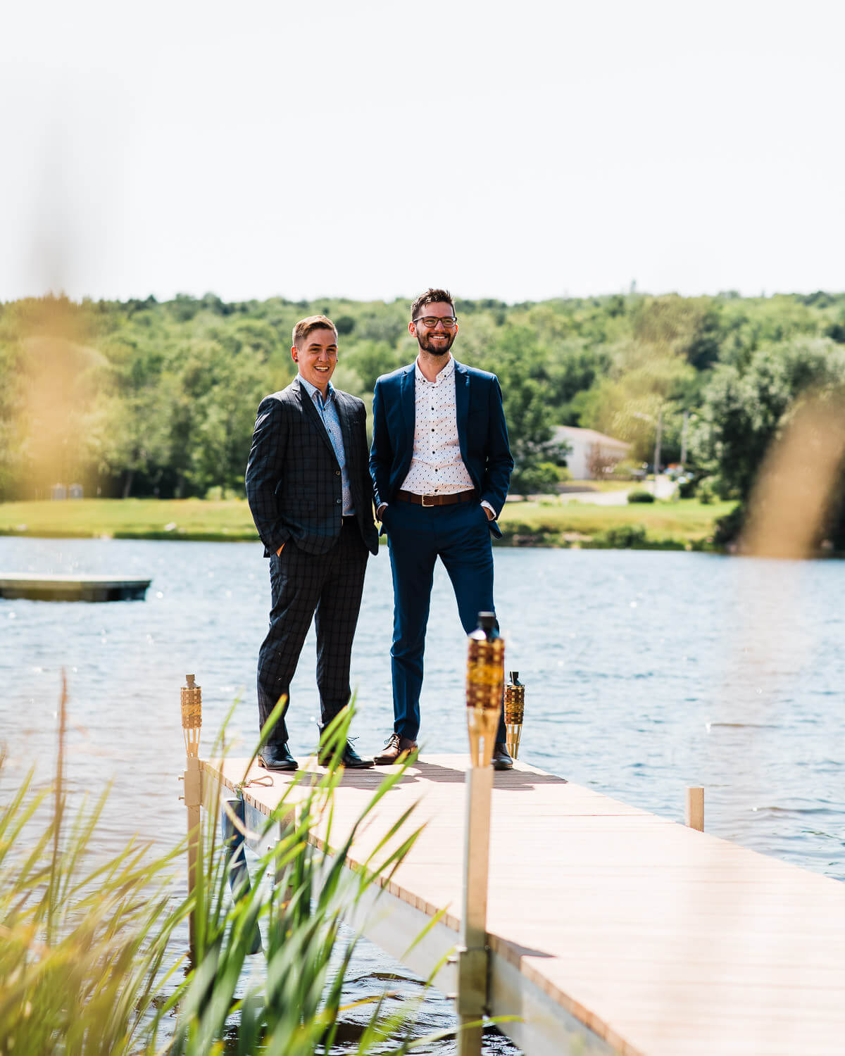two grooms posing for photos on the dock at a halifax wedding
