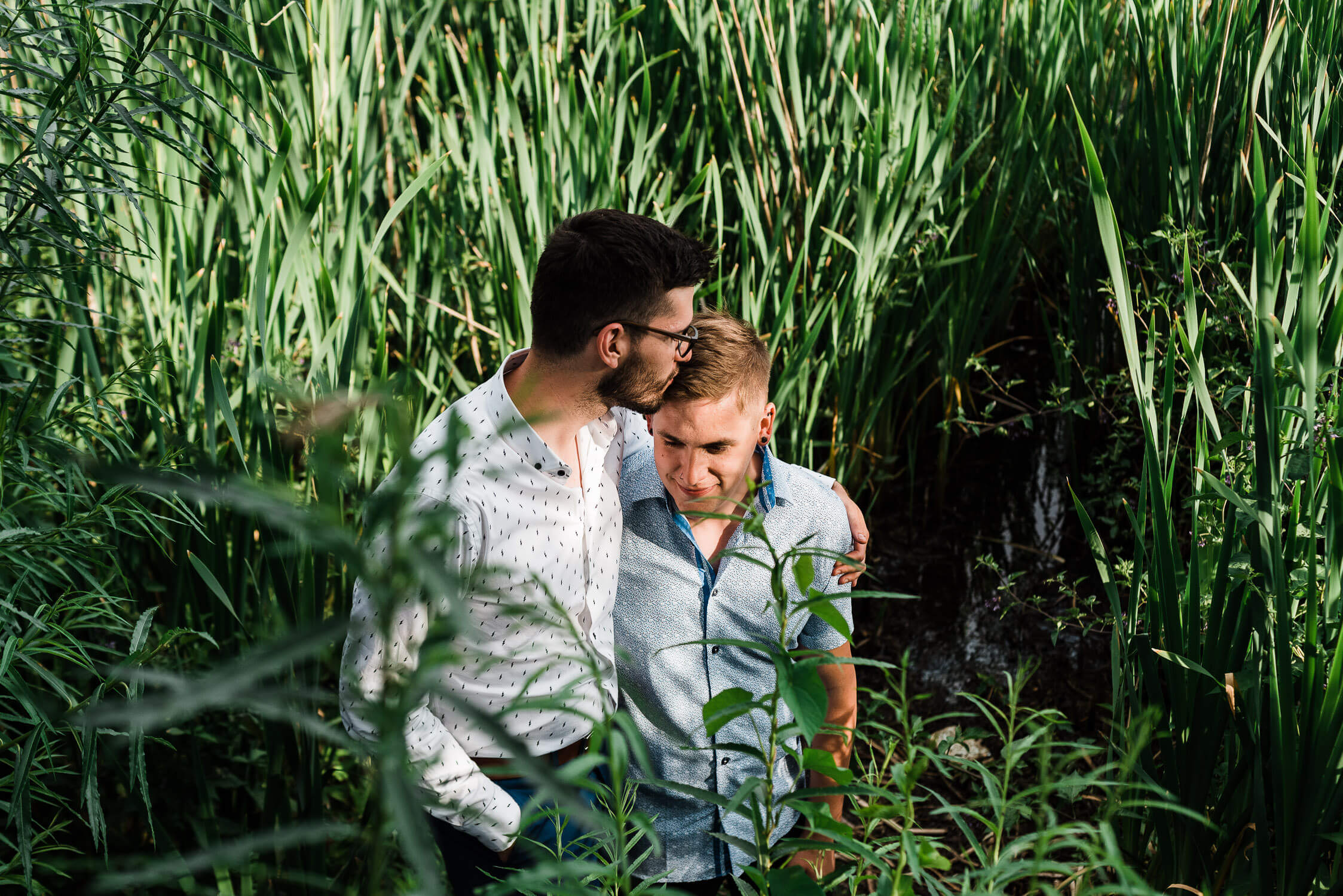 Two men embracing in tall grass near the lake