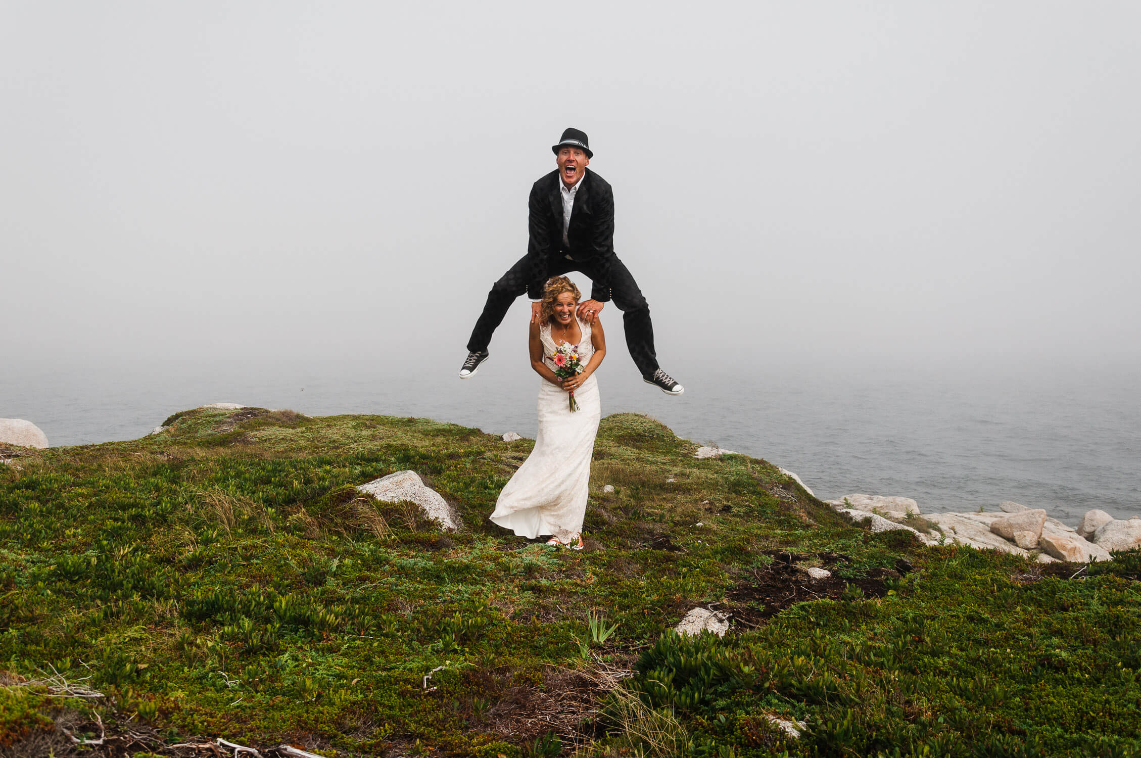 Groom jumping, leap frog style, over bride's shoulders