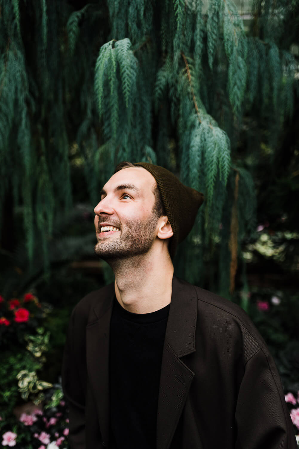 Young man wearing brown jacket and hat, laughing while surround by plants at Allan Gardens in Toronto