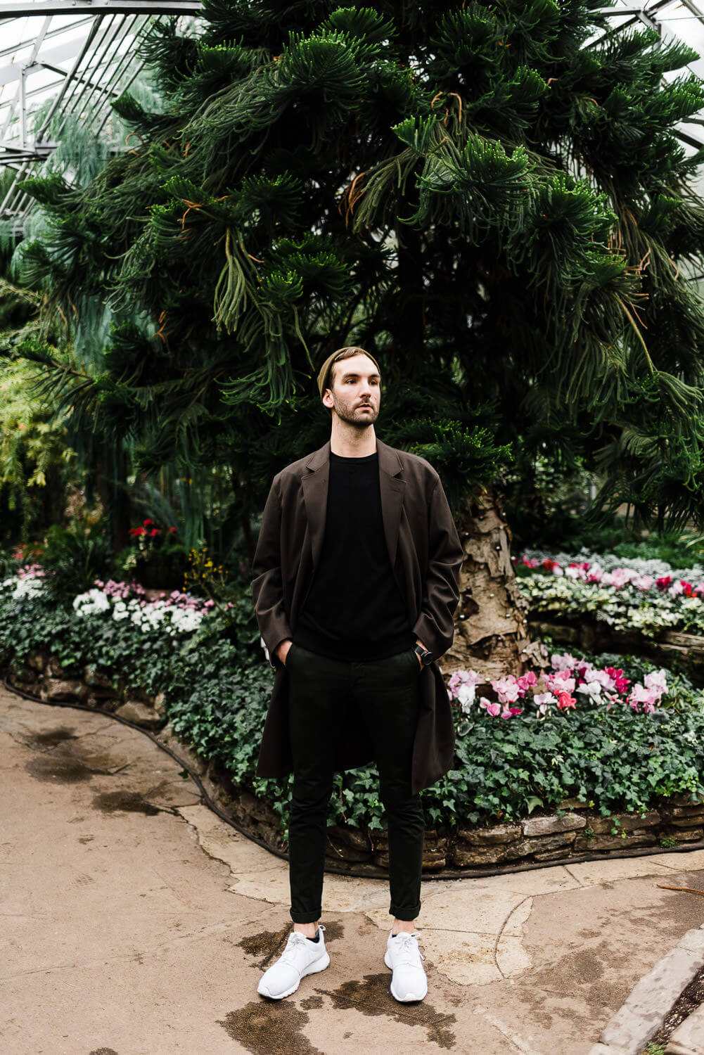 Very tall young man poses for portrait at Allan Gardens in Toronto