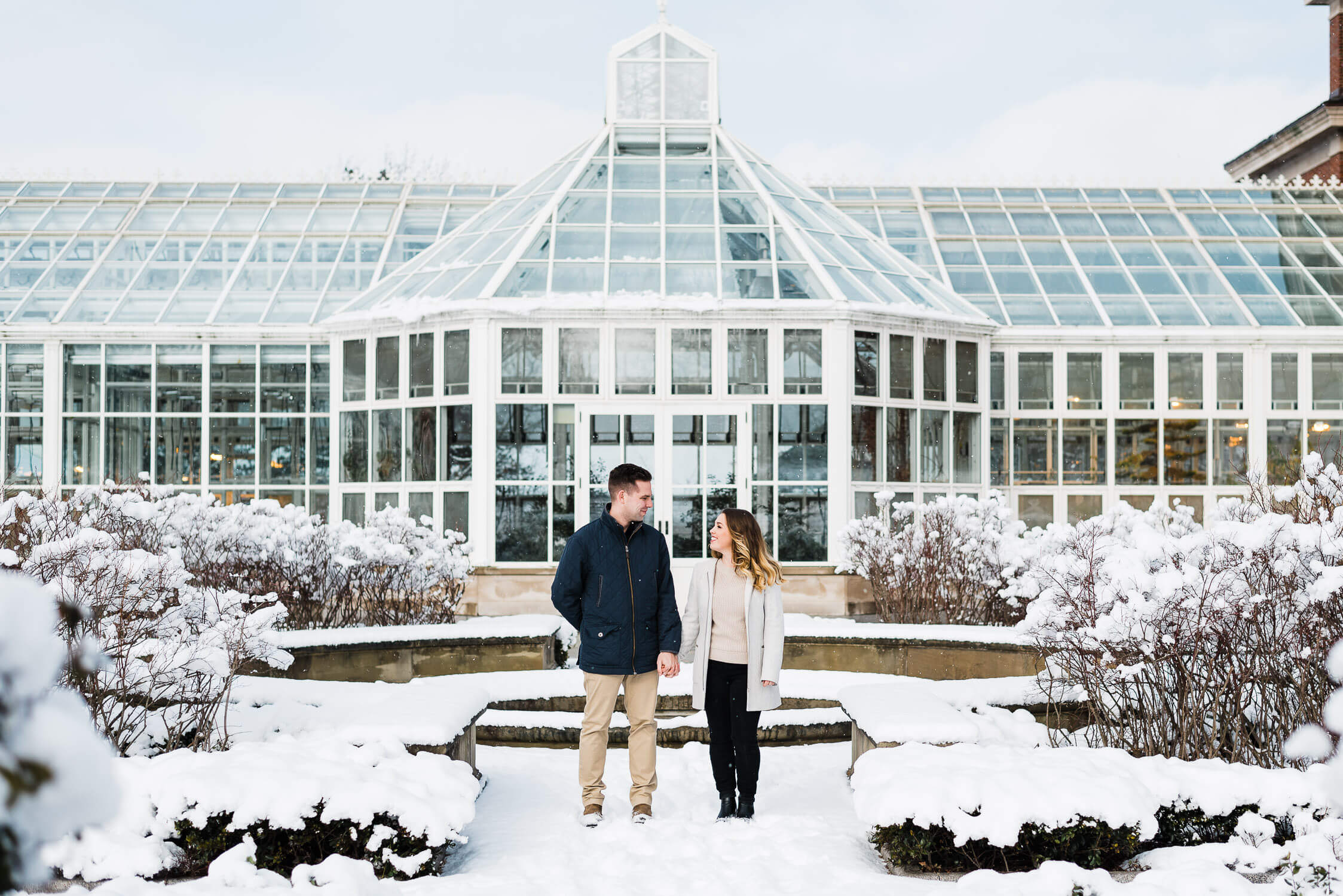 Engaged couple stand in front of Harriett Irving Gardens in Wolfville