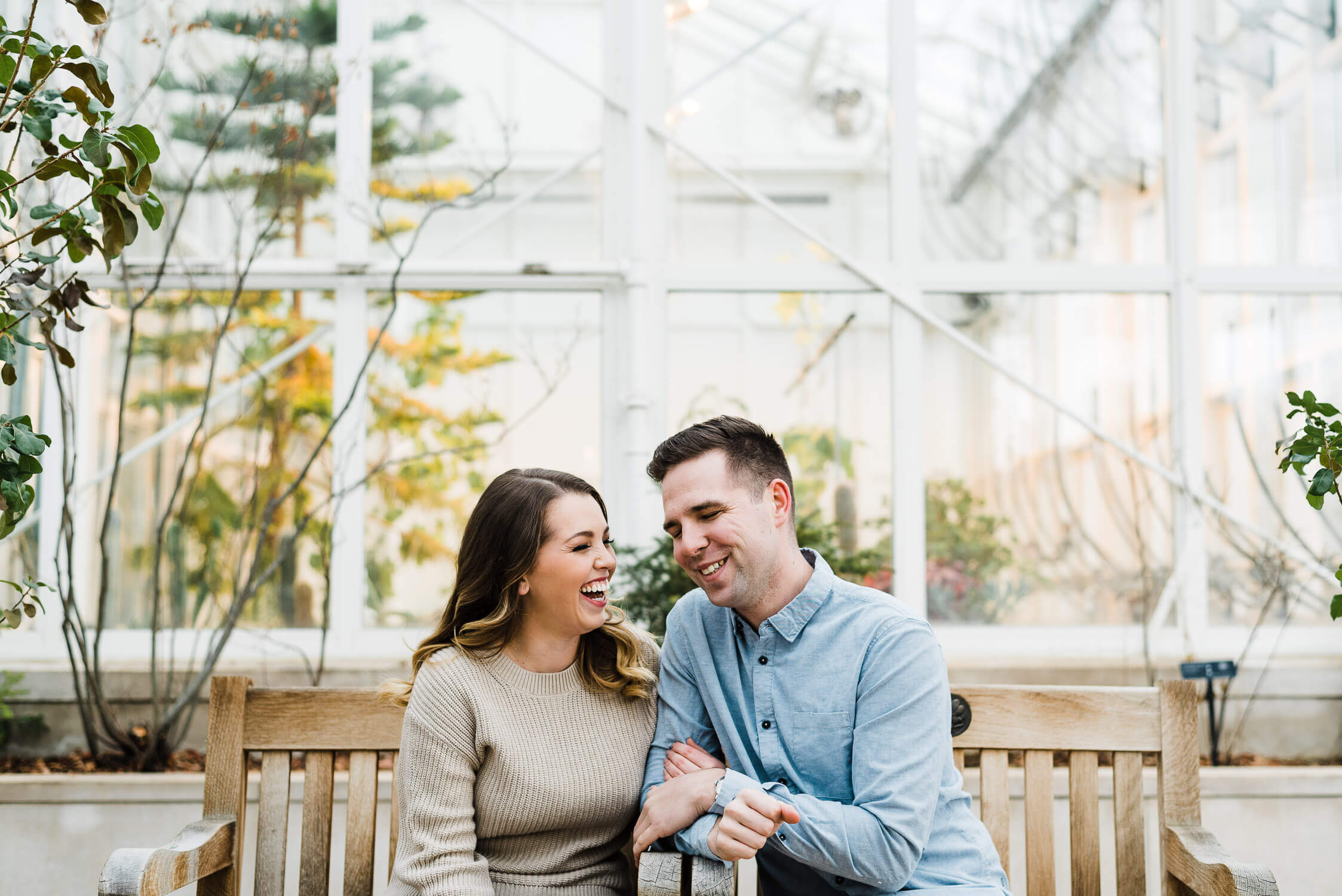 engaged couple laughing in greenhouse