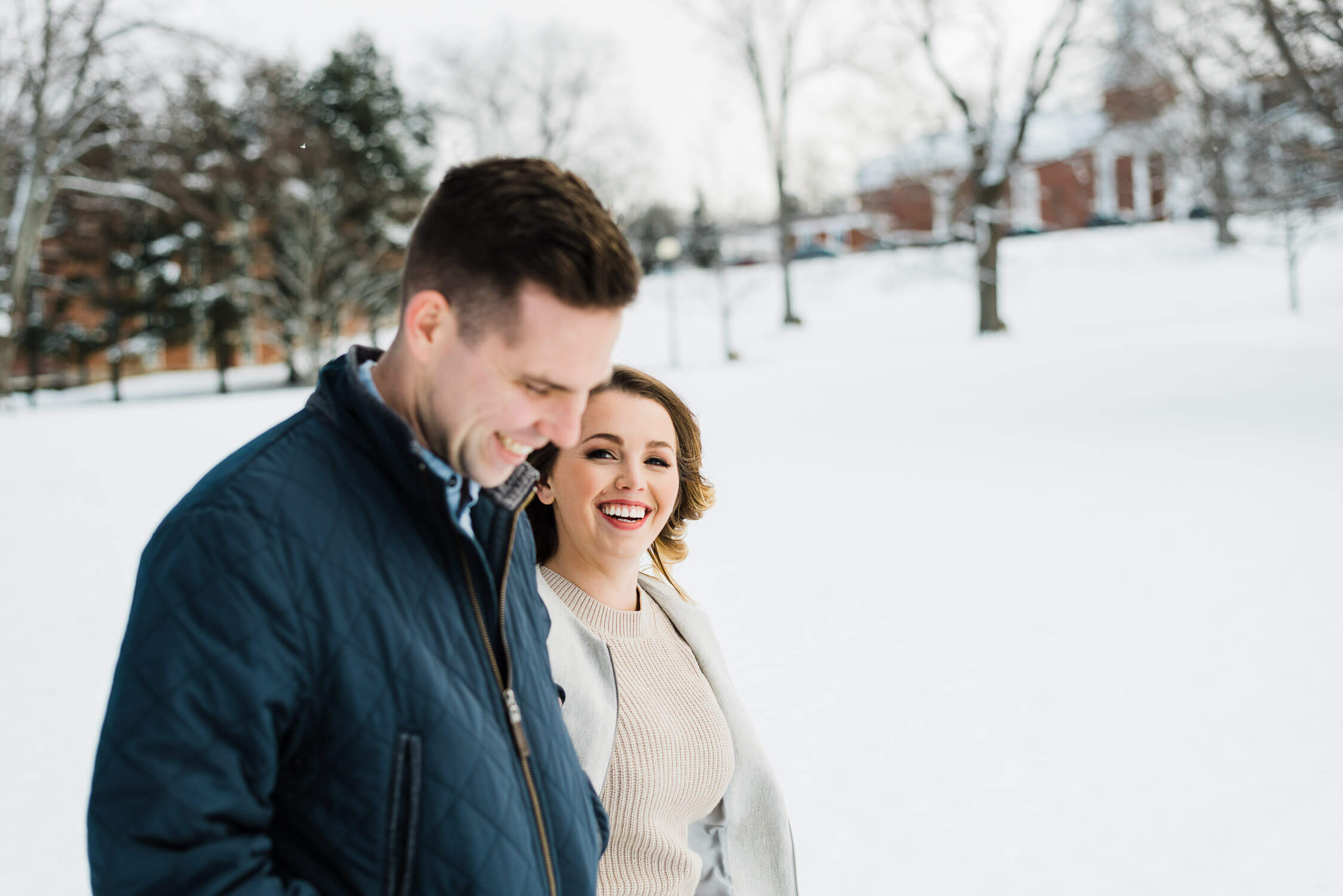 Woman laughing at her partner as they walk through the winter snow